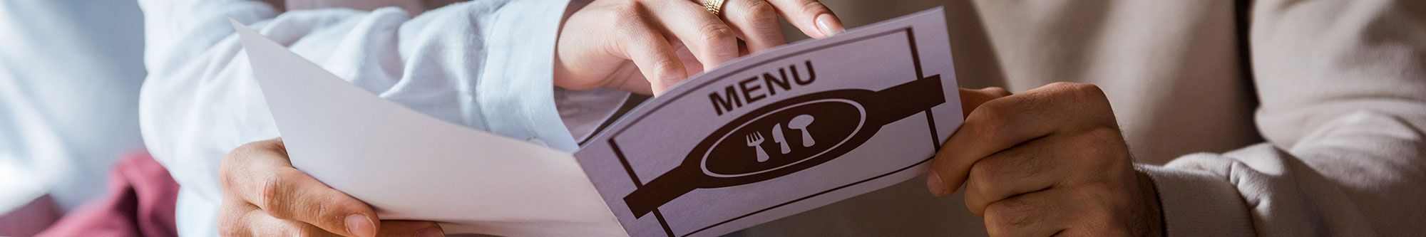 Woman finger pointing at menu in restaurant